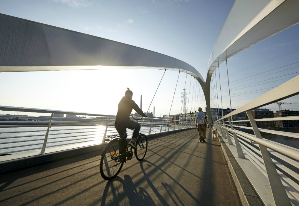 A cyclist and a walker with a dog crossing a bridge.
