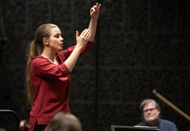 female in red dress directing