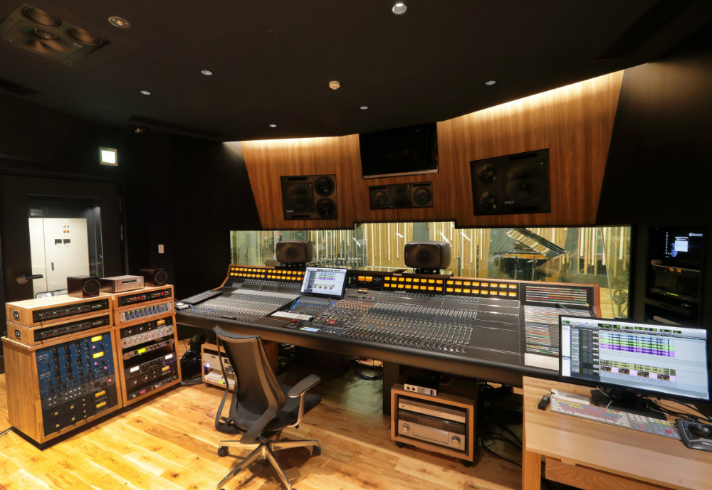 Recording studio with mixing table and speakers.