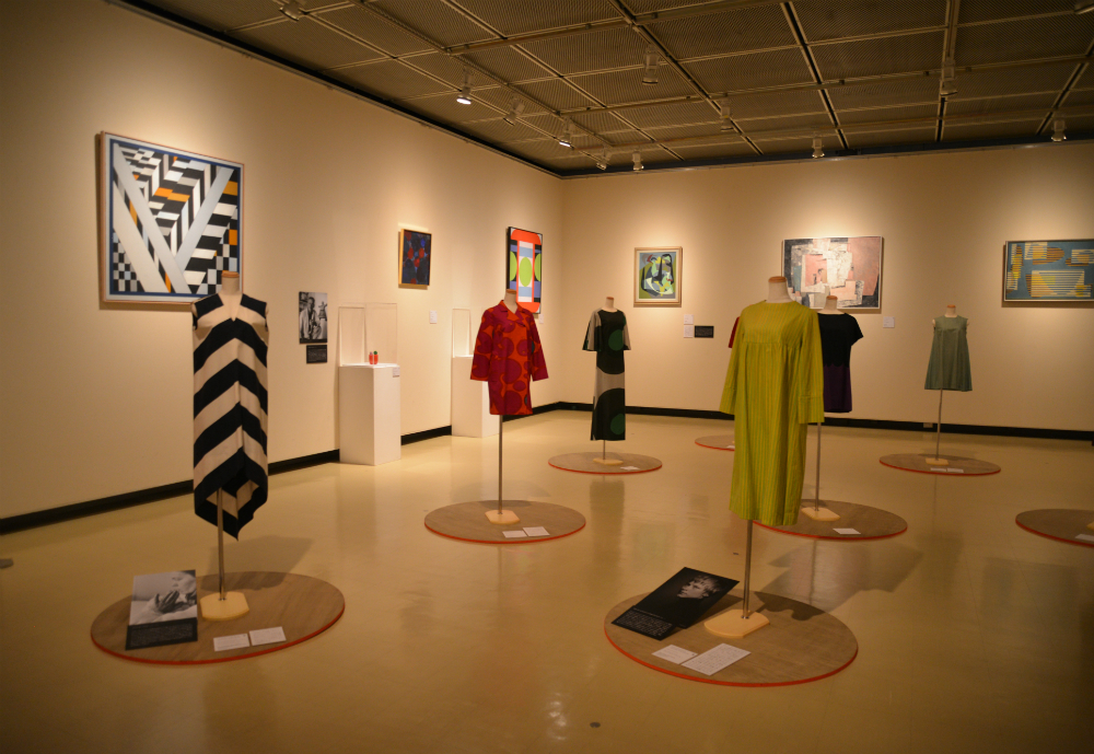 Textiles and paintings on display in a museum.