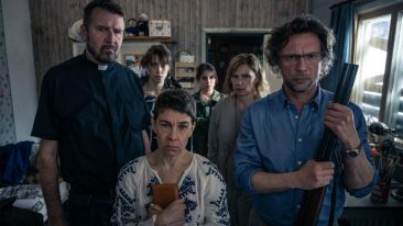 Five people with serious expressions and one of them holding a shotgun.
