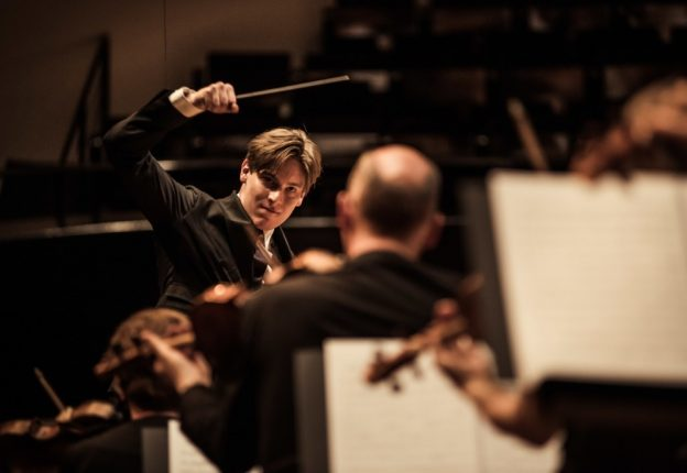 young man conducting orchestra