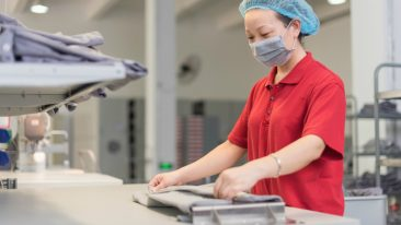 Woman folding a shirt in industrial setting.