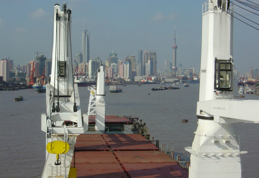 Cargo ship with cranes approaching a city.,