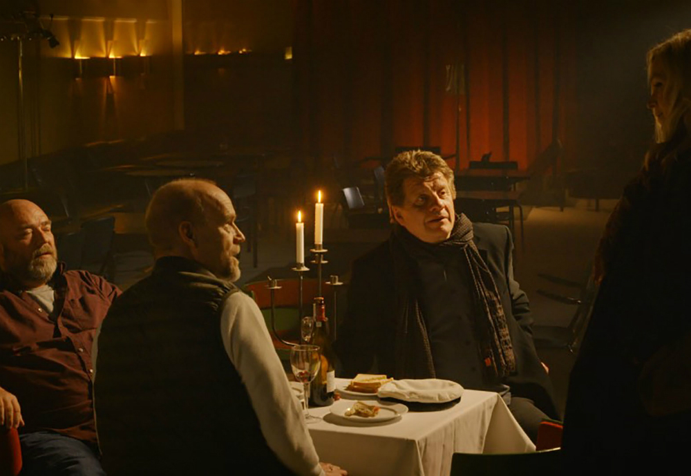 A standing woman talks to three men seated at a table.