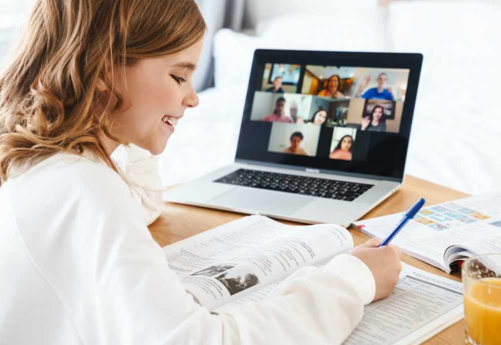 Girl writing in textbook with open video chat session on computer.