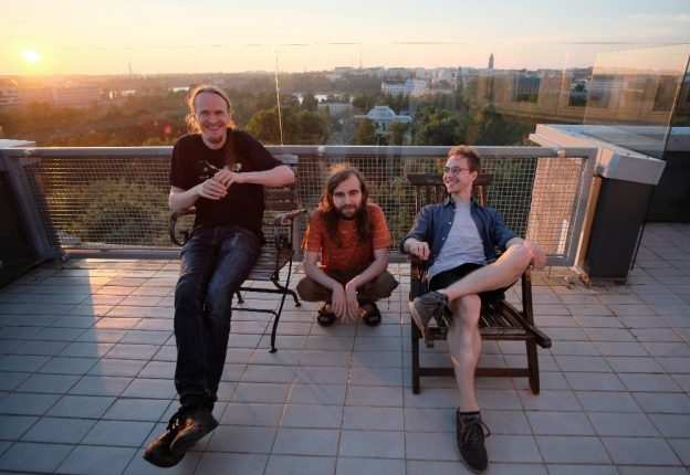 three men smiling on rooftop