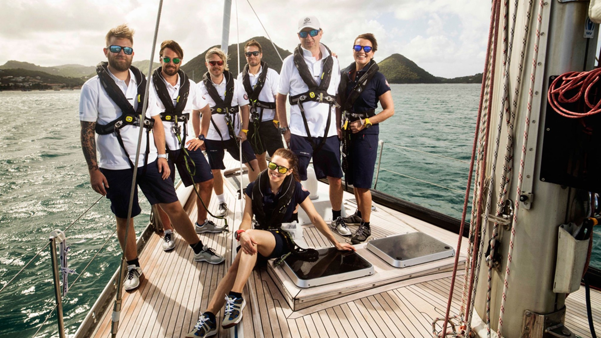 A group of people standing on a sailing boat