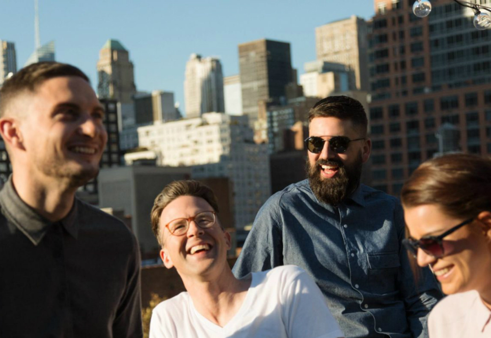 Four people laughing on a rooftop.
