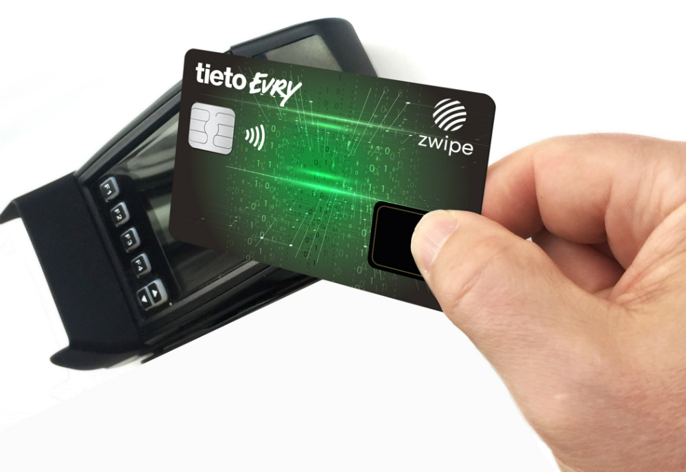 A credit card with biometric payment held against a card machine.