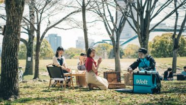 Food courier makes a delivery to Japanese women in a park.