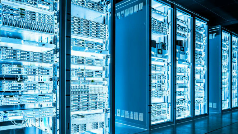 Racks of computing infrastructure in a facility lit up in blue.