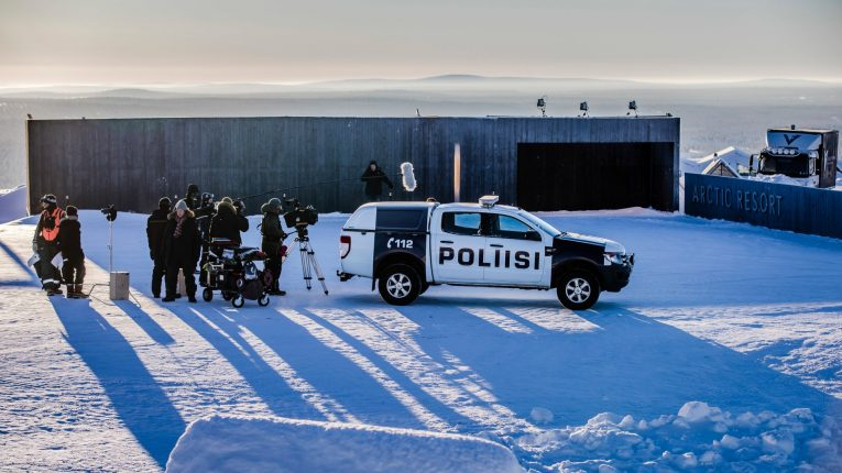 A police vehicle surrounded by a film crew in a winter landscape