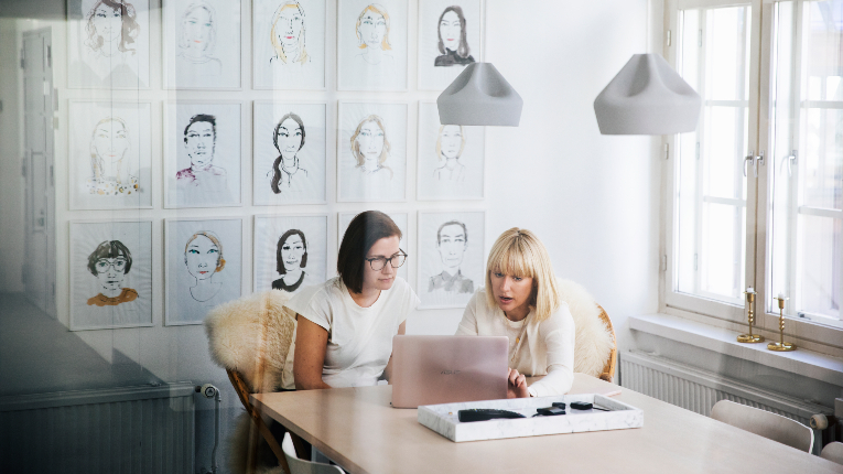 Two women working at a laptop