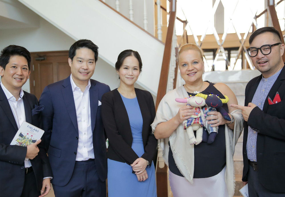 A blonde woman holding soft toys and smiling together with four suited Asian men and women
