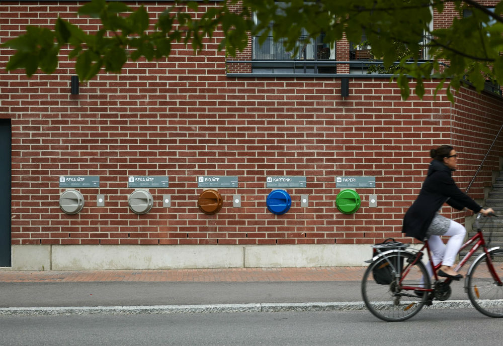 Woman cycling next to a recycling station attached to a brick wall