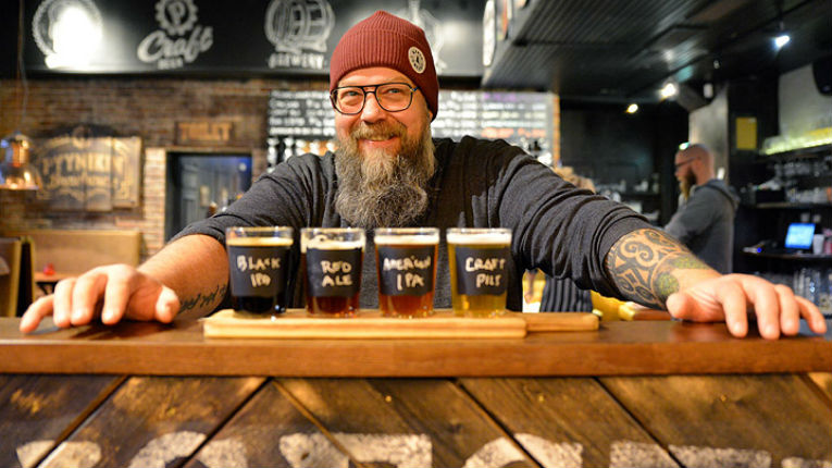 Bearded man smiling behind four pints of beer