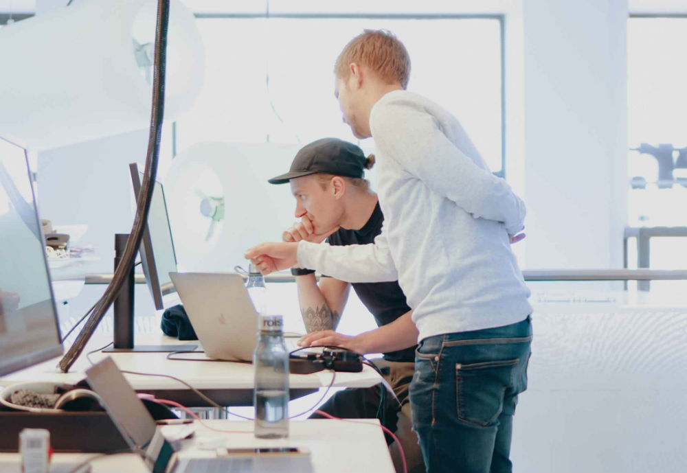 Two men looking at a computer in an office