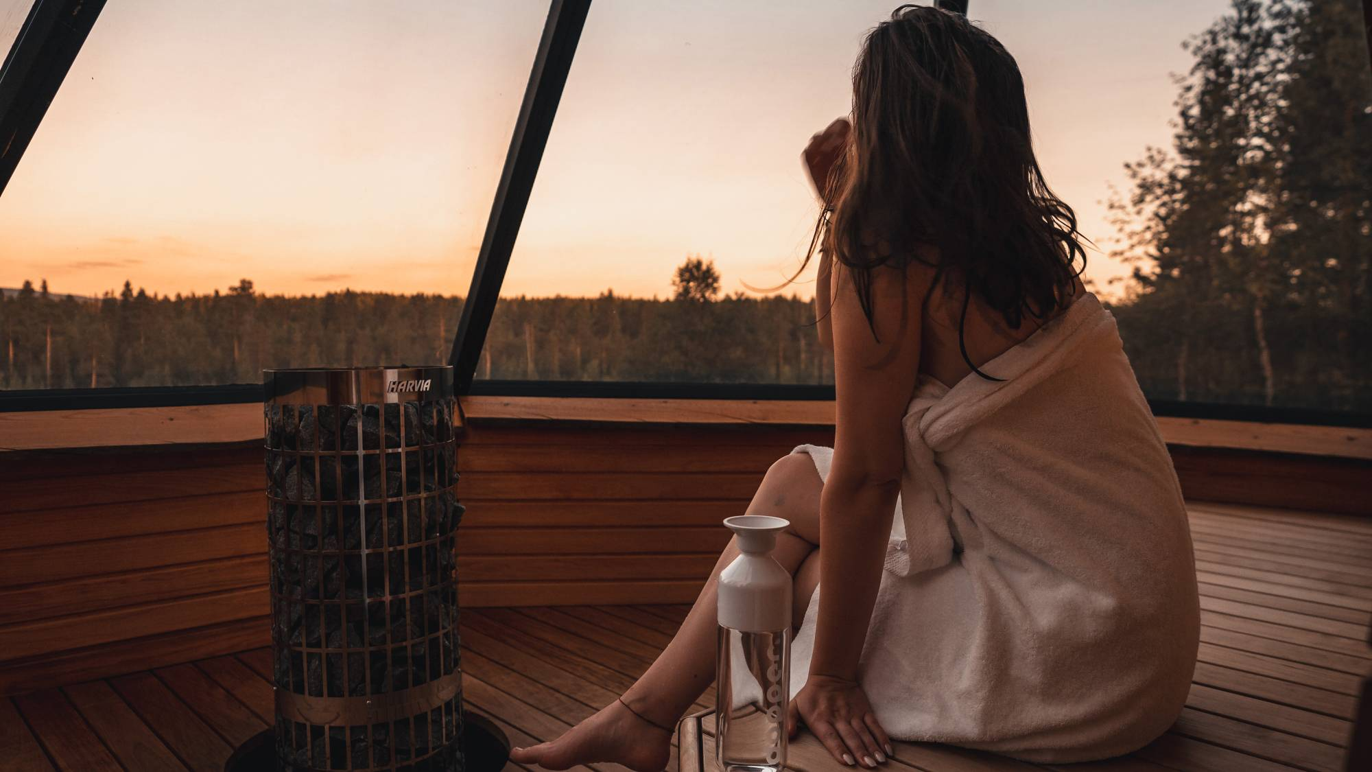 A woman in sauna gazing at the treeline.