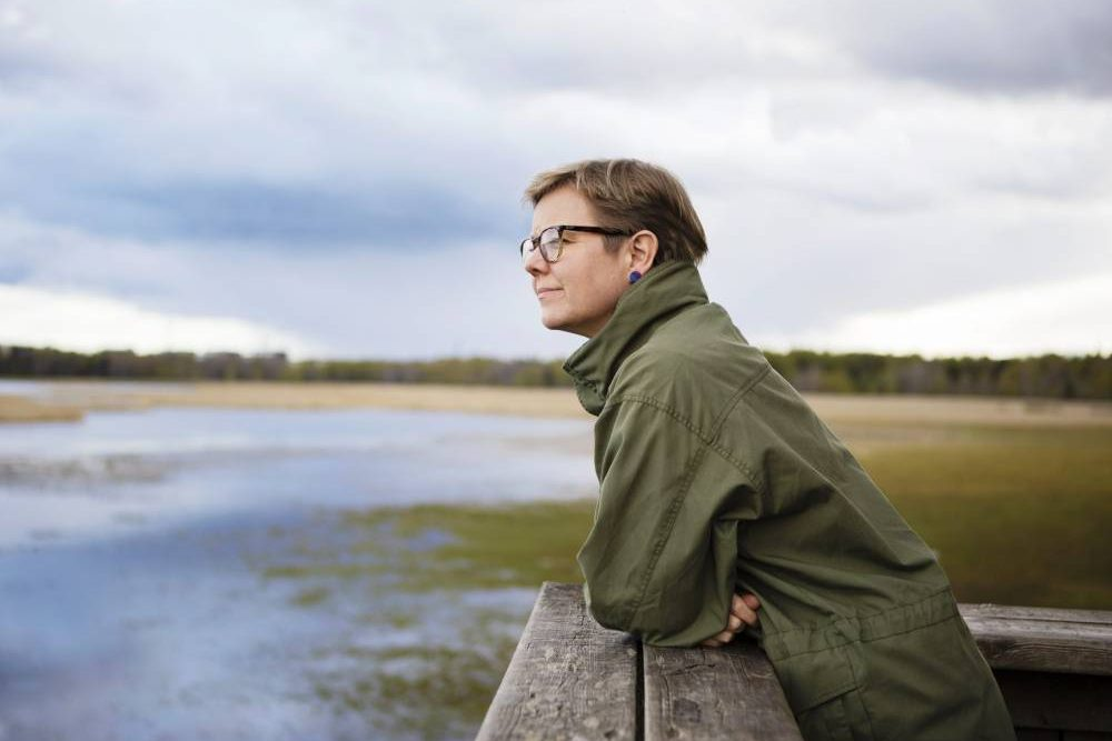 Finnish minister looking across lake in green coat