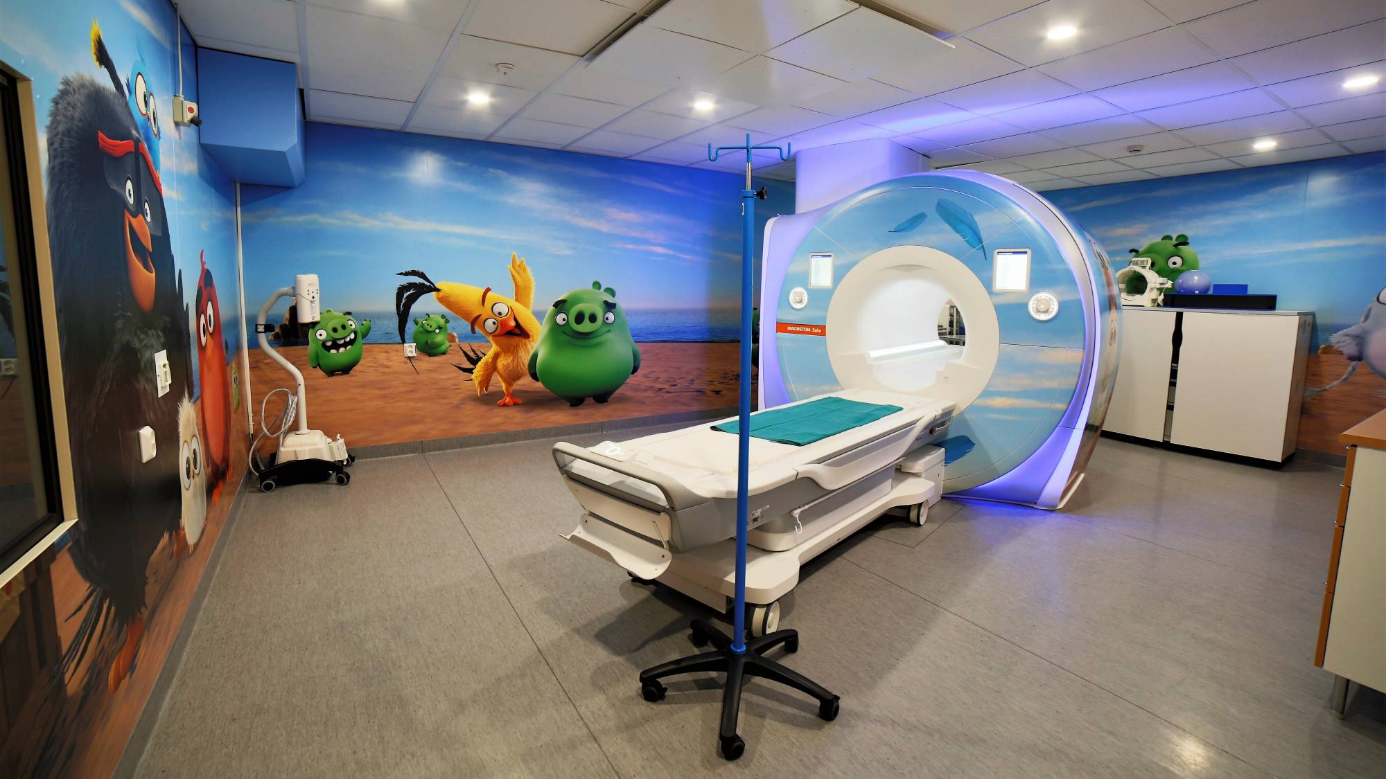 An MRI machine and other hospital equipment in a colourfully decorated room.