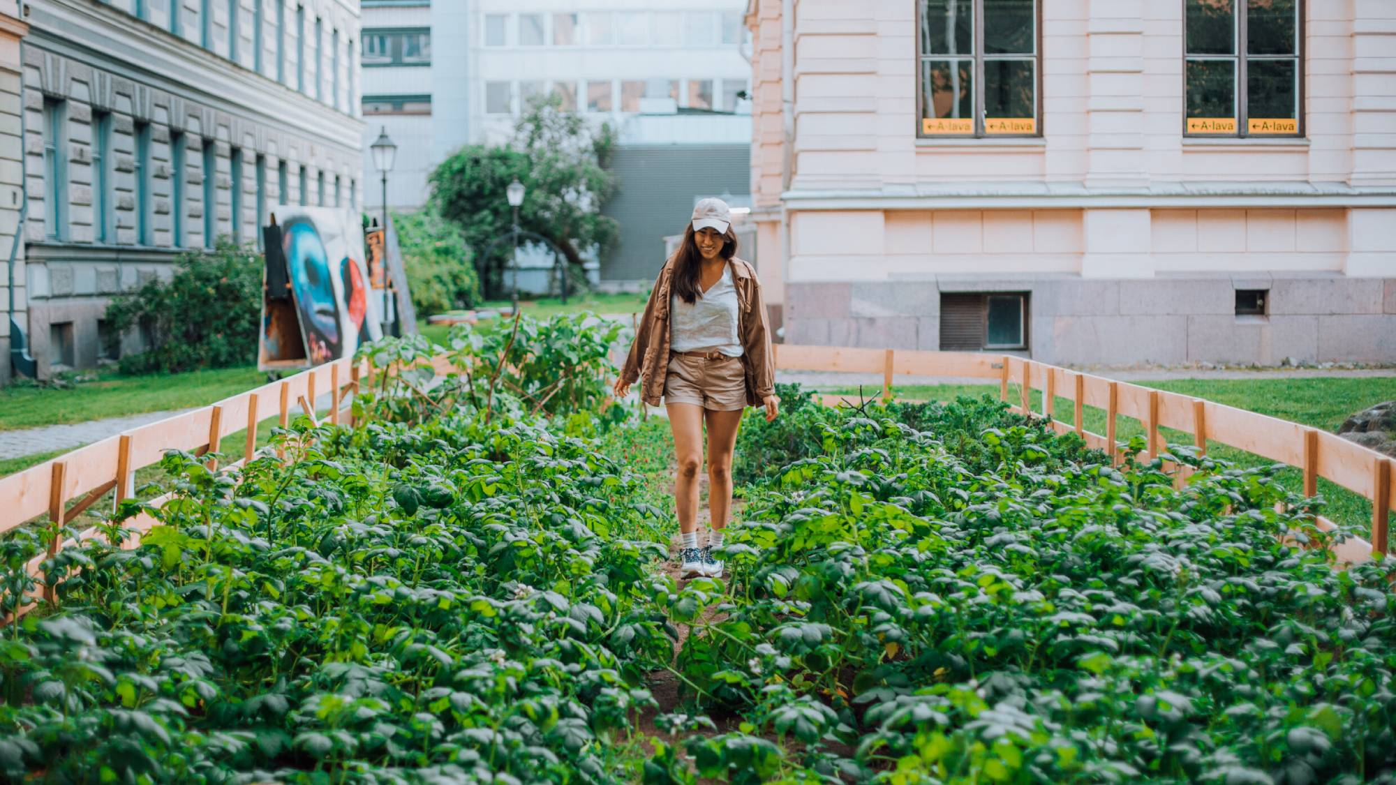 A woman standing in the middle of greens in an urban garden.