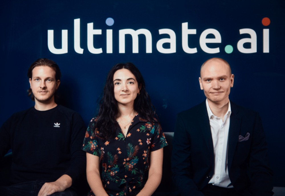 Three people sit and smile under a ultimate.ai sign