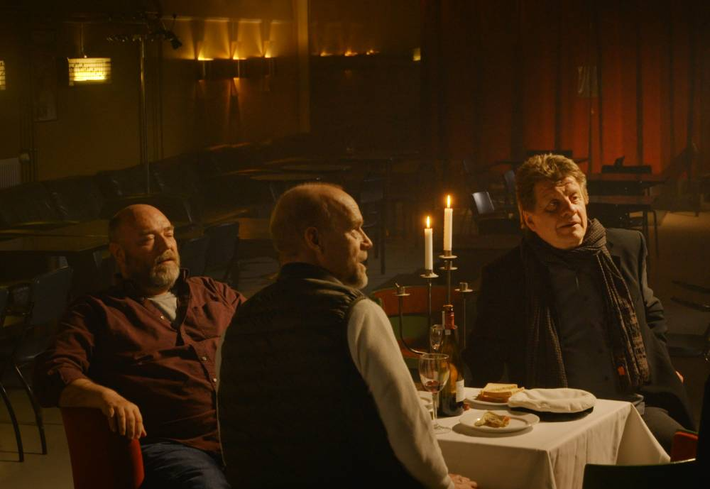 three men sitting at a dimly lit bar