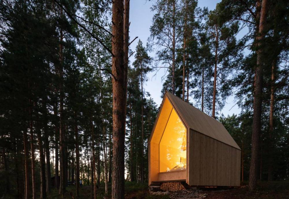 the Kynttila (candle) cabin illuminating a quiet forest