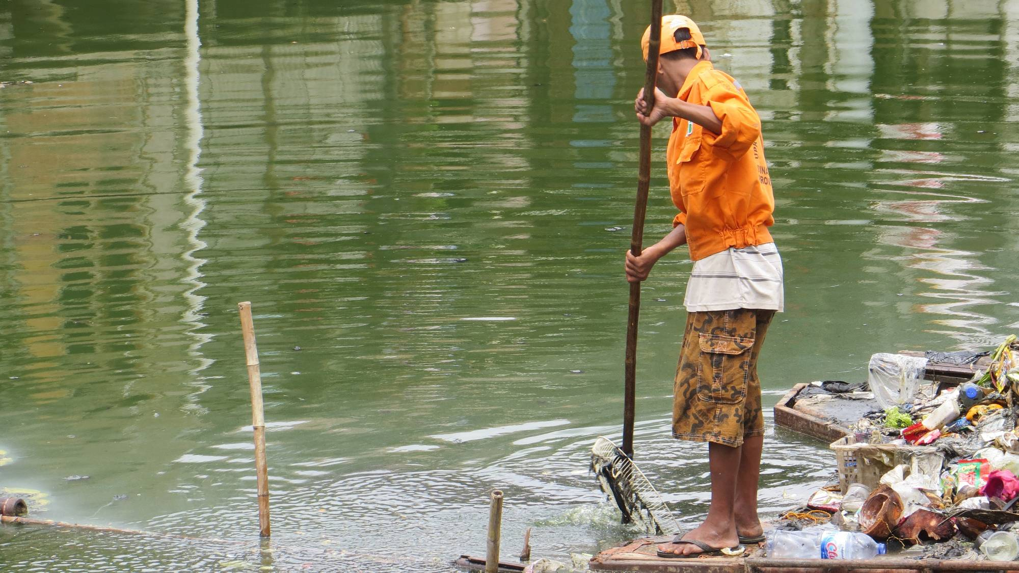 A man picking up waste standing on a raft in a river.
