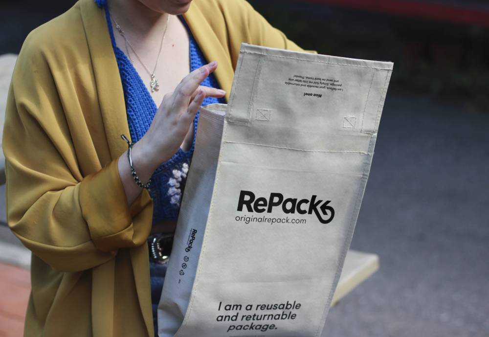 woman holding a reusable postal package