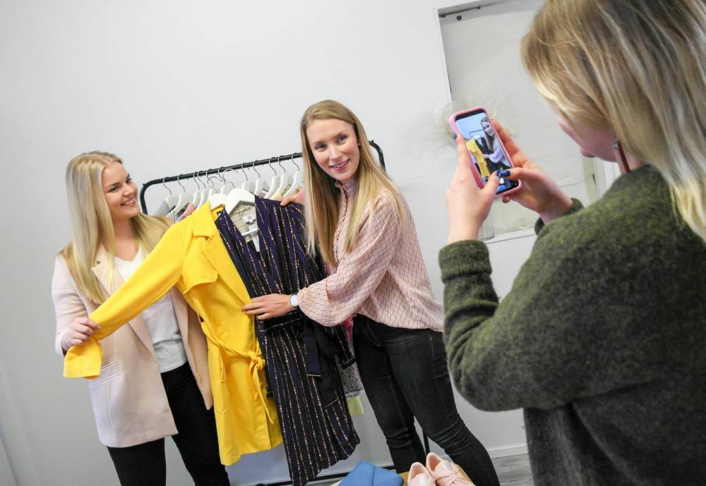 women holding up clothing to a third woman capturing them by phone