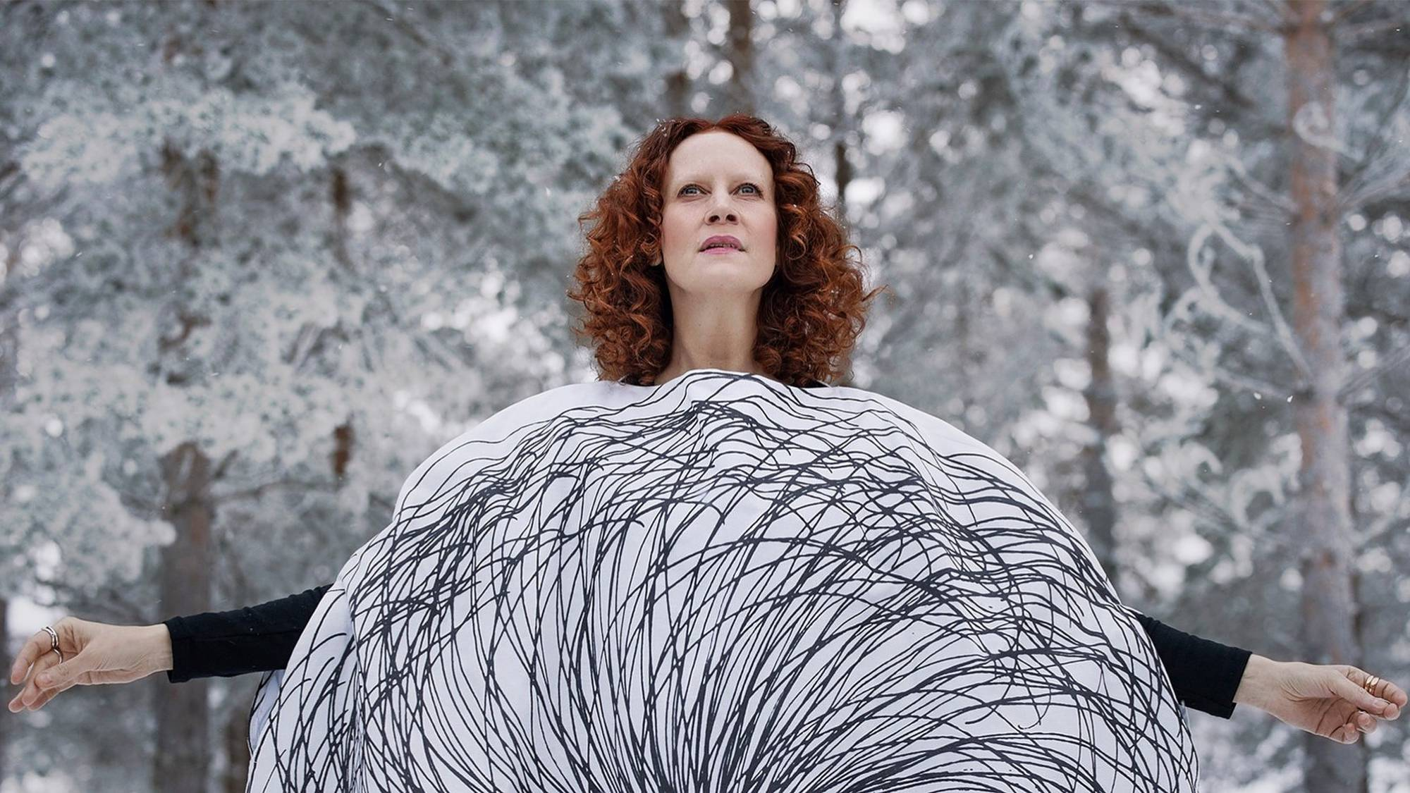 red-haired woman, dressed in sustainable clothing looks to the sky