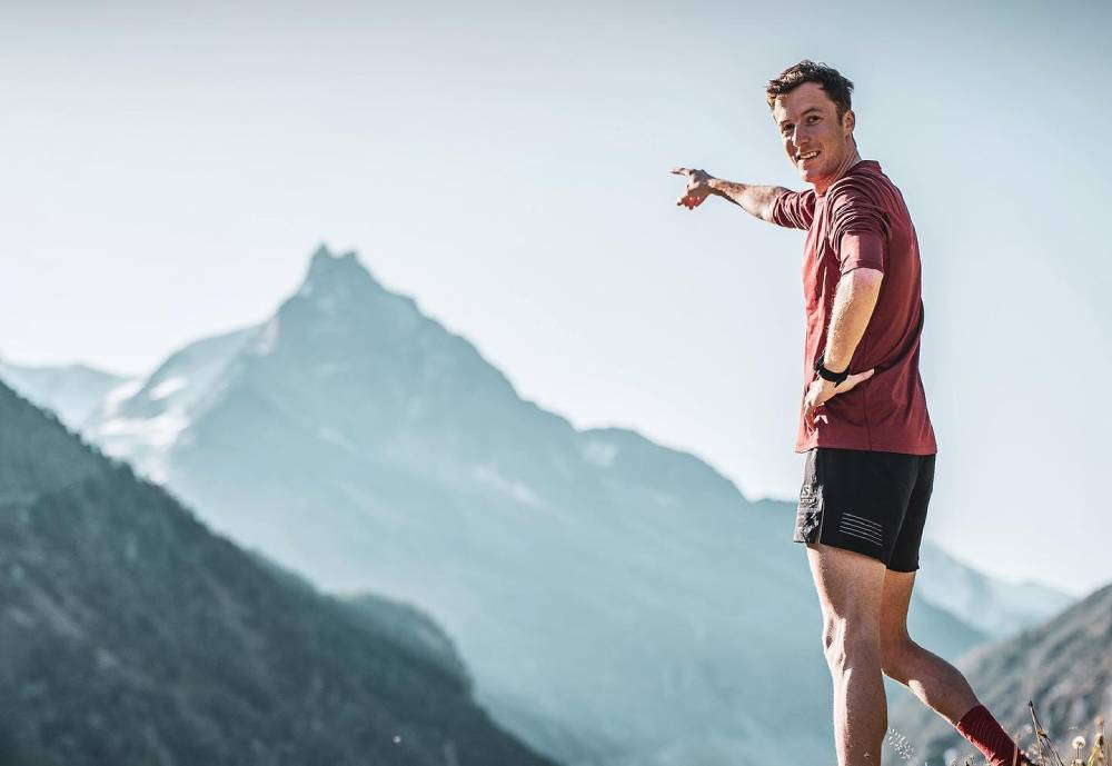 fit male pointing at a mountain top in shorts