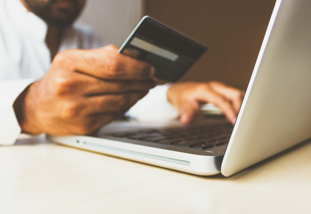 Man holding a credit card next to a laptop