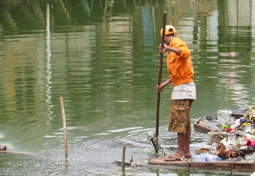 Man on a raft removing plastic from a river