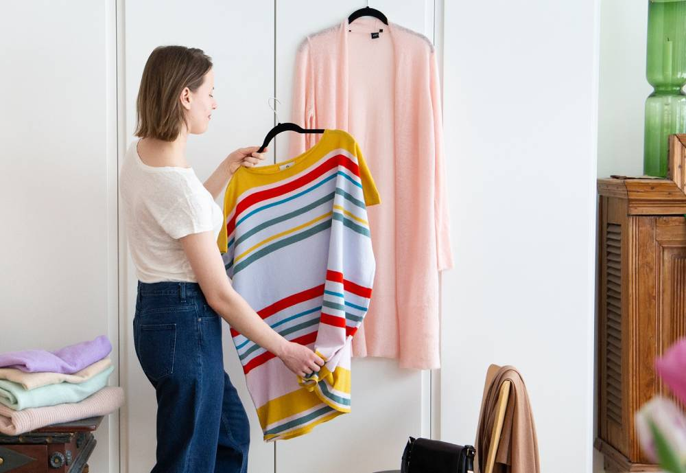 woman arranges clothing on hangers