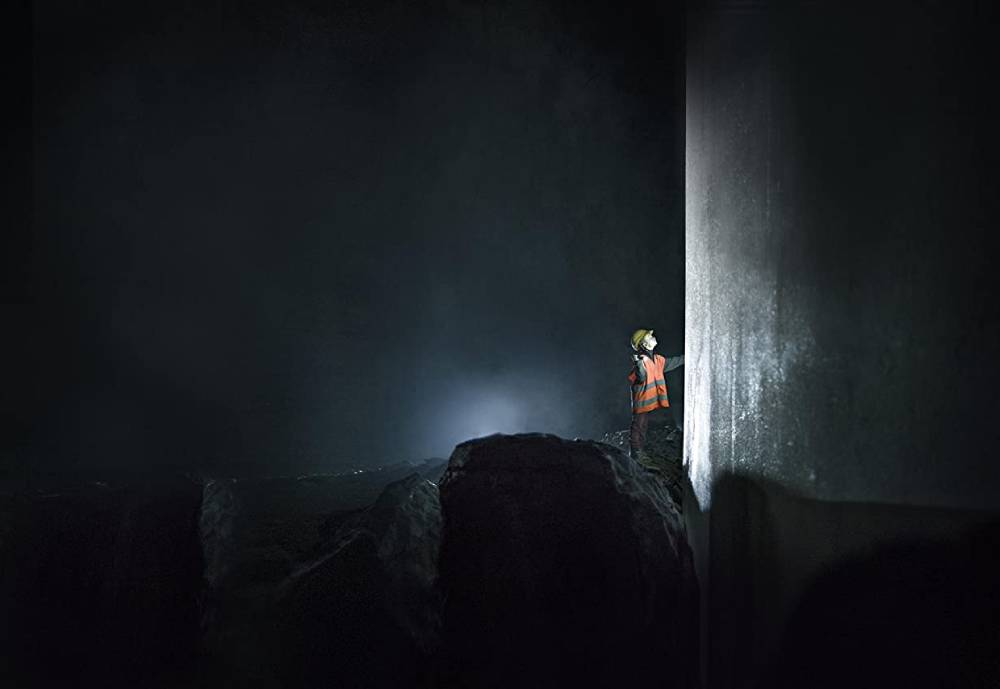 construction worker in the dark looking at high wall