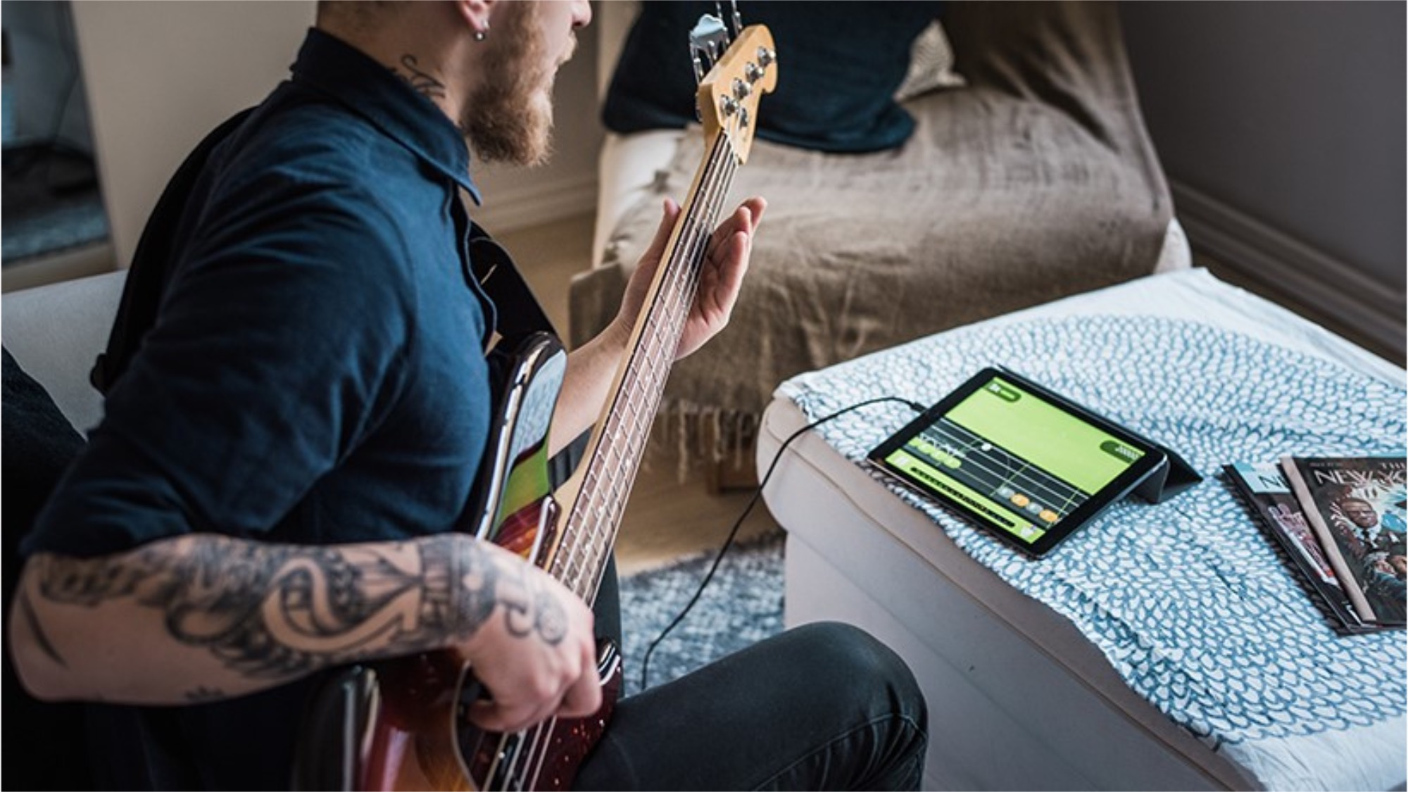 Tattooed man playing guitar with a music app