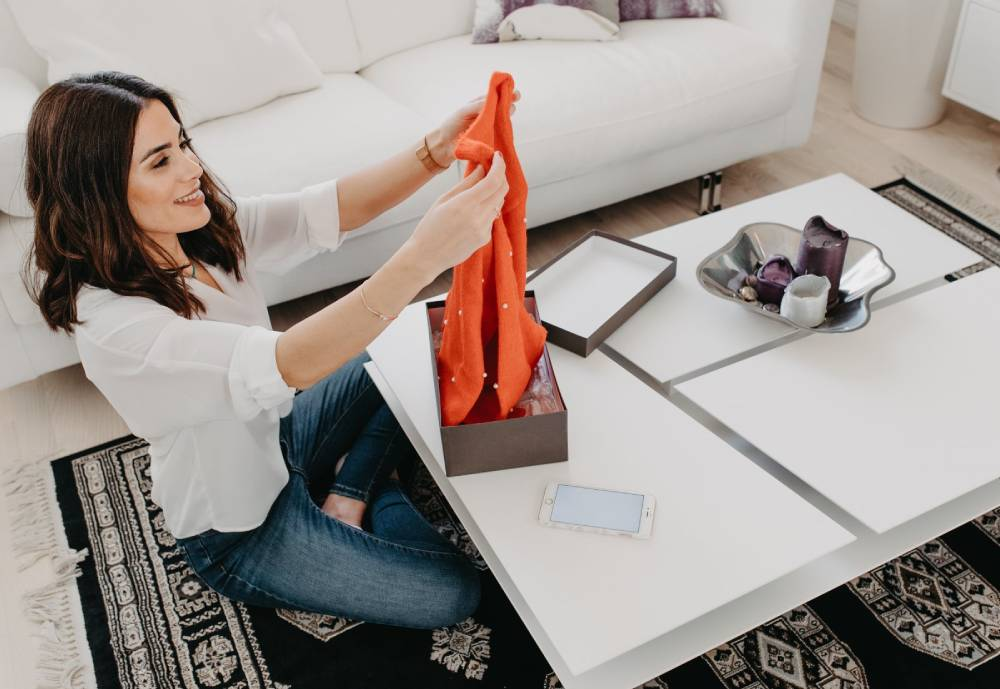 woman opening a package and admiring clothing that was inside