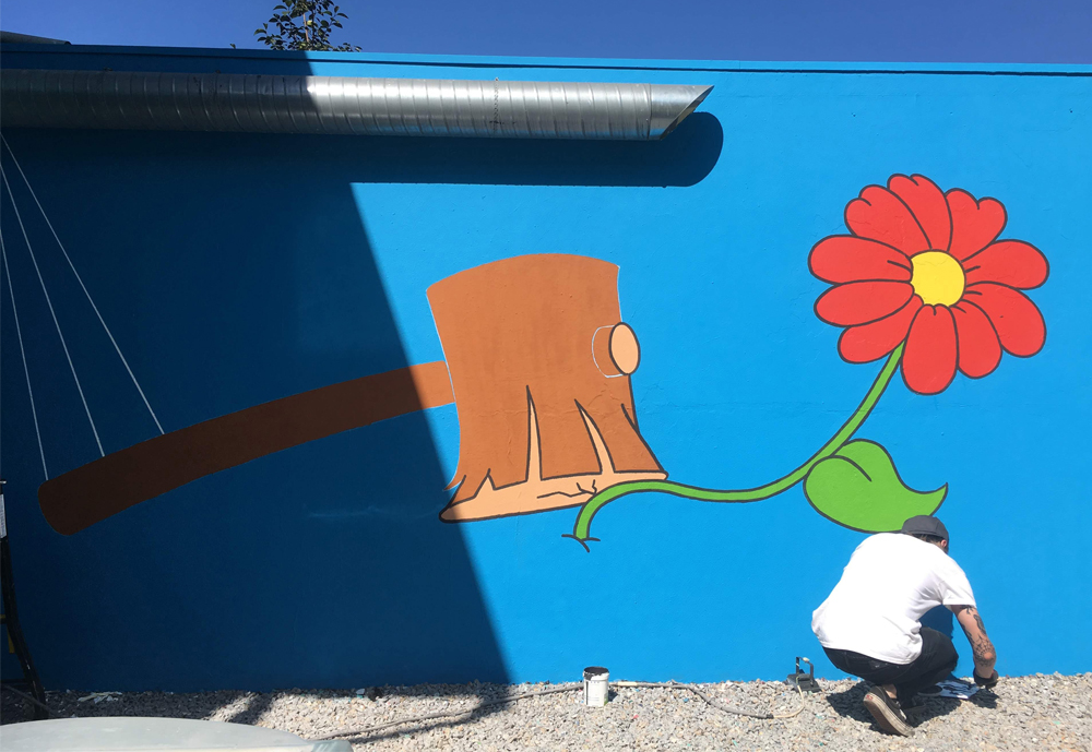 Illustrator Mikko Heino painting a wall