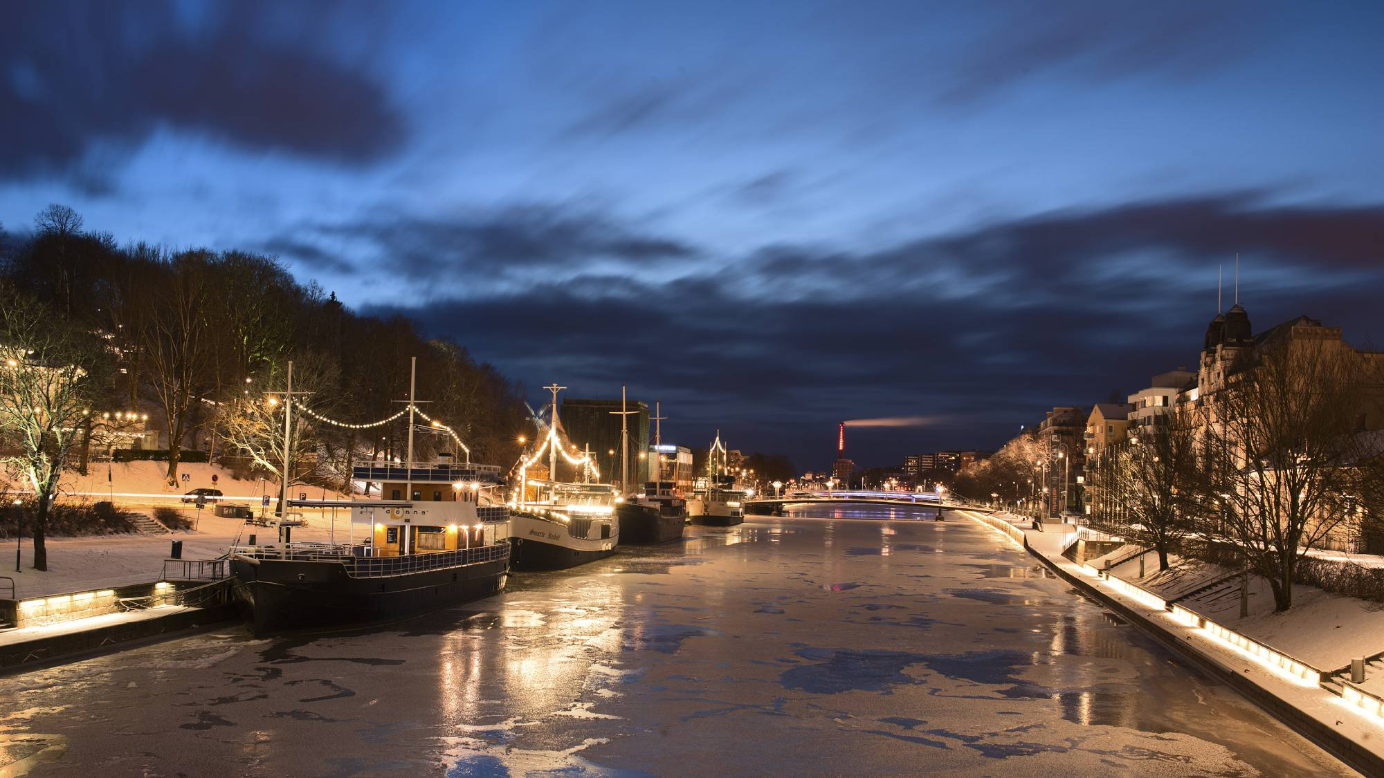 Boats by a partly frozen river at night time.