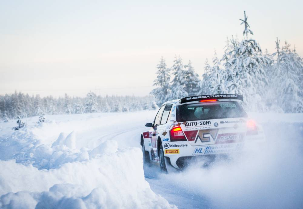 rally car driving down a snowy road