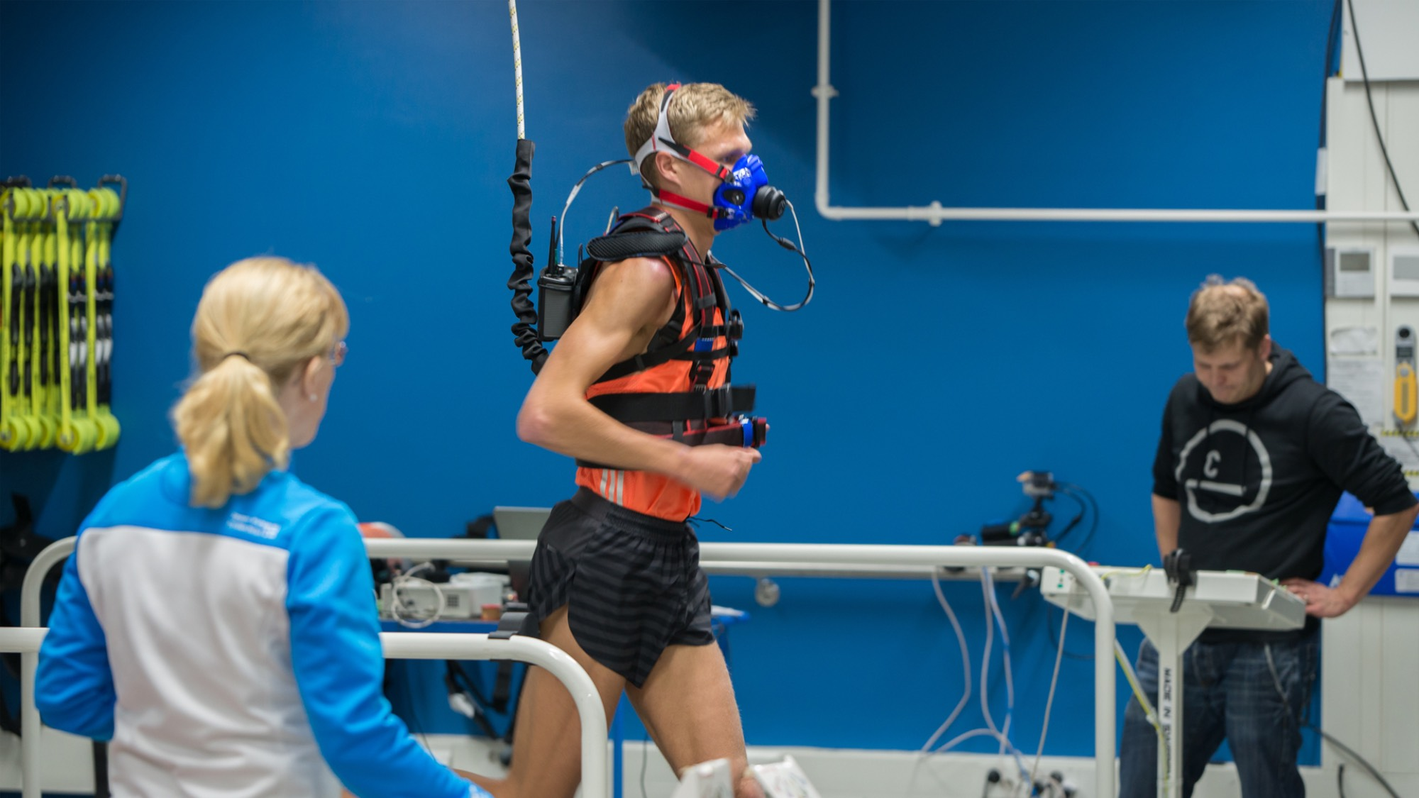 An athlete with an oxygen mask running on a treadmill with physicians watching