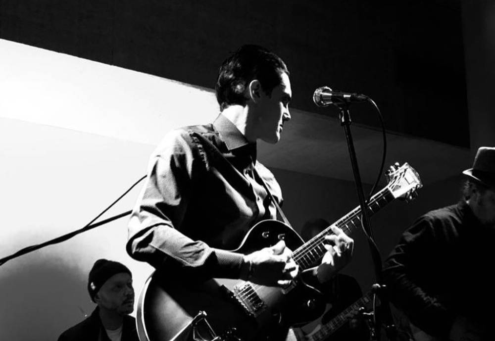 Artist Bobby Oroza performing on stage in a black and white photo