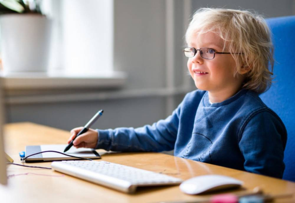 young boy using computer track pad