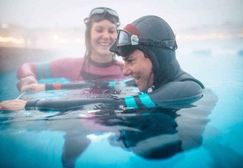 Two women in diving gear in a swimming pool