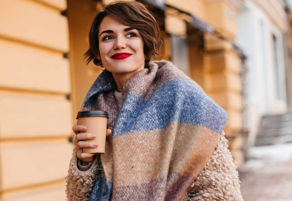 woman smiling with cup of coffee in her hand