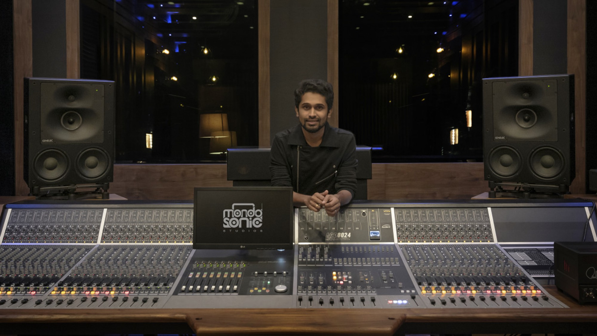 Man sitting by a mixing desk in a music studio