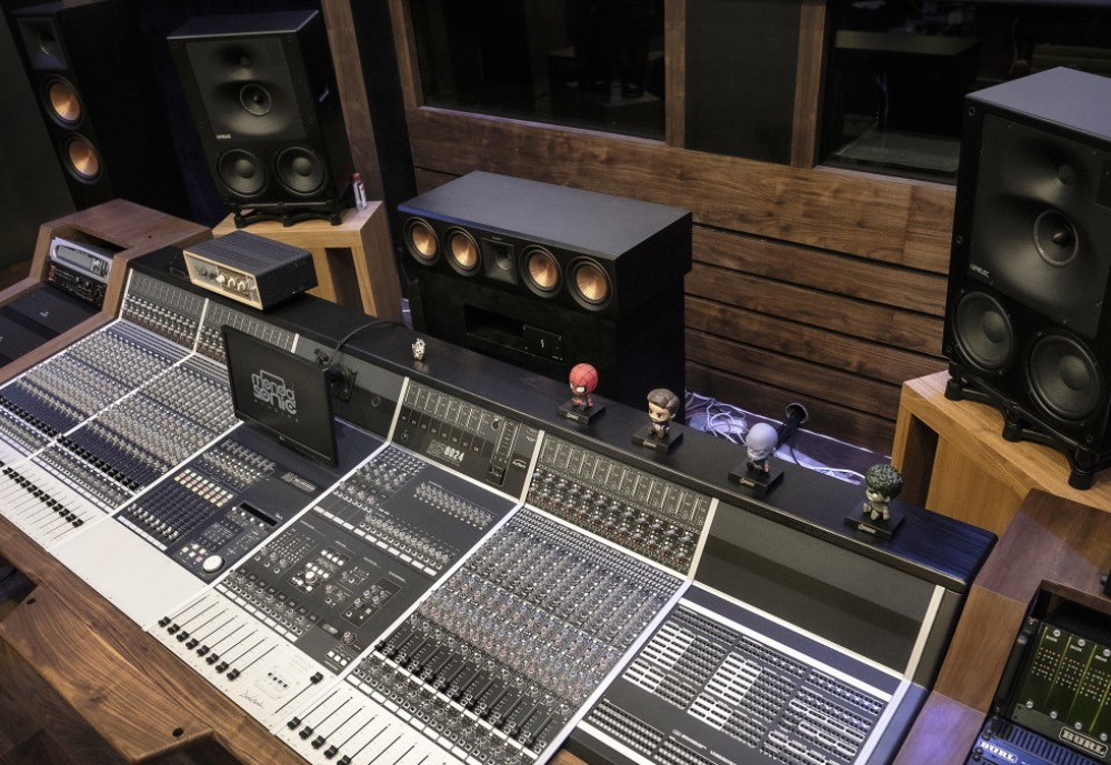 A mixing desk and several speakers in music studio